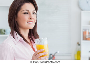 Close-up of smiling woman with orange juice