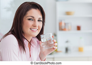 Close-up portrait of woman with glass of water - Close-up...