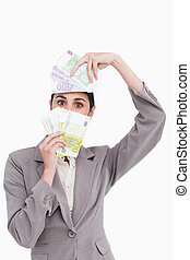 Business woman holding fanned banknotes over face - Portrait...