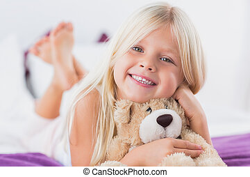 Little girl with her teddy bear lying on a bed