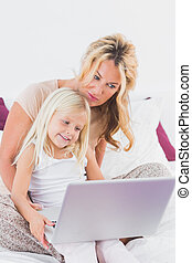 Mother and her daughter using a laptop on a bed