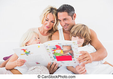 Happy family reading a story together on a bed