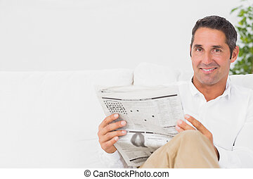Smiling man reading a newspaper in the living room