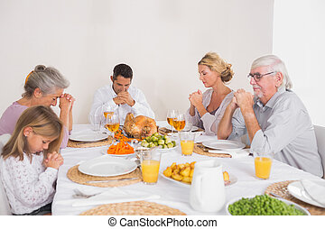 Family saying grace before eating a turkey for dinner
