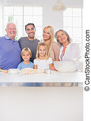 Smiling family posing in the kitchen in front of ustensils