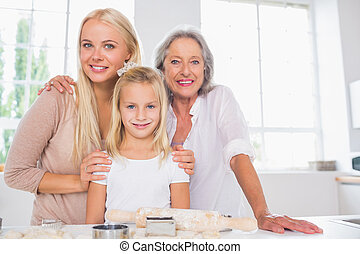 Cheerful mothers and daughters cooking together in the...