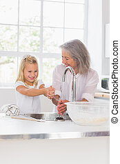 Smiling grandmother and granddaughter washing hands in the...