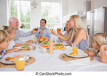 Adults raising their glasses at thanksgiving dinner without...