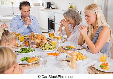 Family praying before dinner - Family praying before...