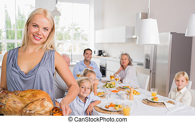 Blonde woman showing the roast turkey