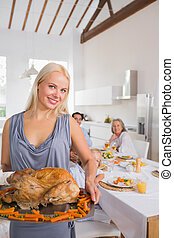 Smiling blonde woman showing the roast turkey
