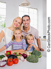 Happy posing family preparing a dinner together