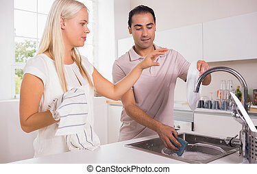 Couple washing dishes together in the kitchen