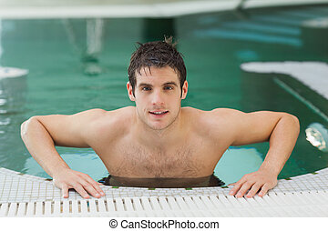 Man getting out of swimming pool - Attractive man getting...
