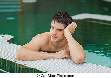 Smiling man relaxing in the pool - Smiling man relaxing and...