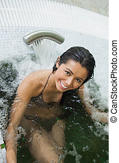 Woman enjoying the hydrotherapy poo - Smiling woman enjoying...
