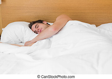 Attractive man asleep in bed in hotel room