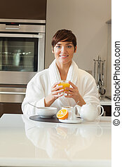 Woman in bathrobe having healthy breakfast in kitchen
