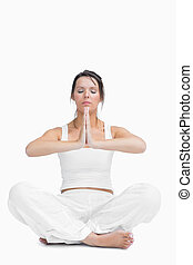 Young woman with crossed legs in praying position over white...