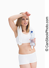 Portrait of young sporty woman holding water bottle and wiping sweat with hand over white background
