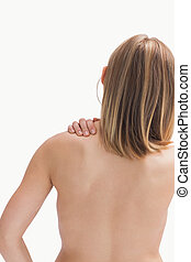 Rear view of topless young woman with shoulder pain