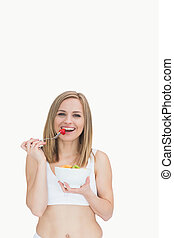 Portrait of happy woman eating from a bowl of fruits