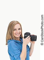 Portrait of happy female photographer with photographic...