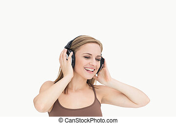 Young woman listening music through headphones over white...