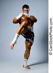 Kick-boxer training before fight on a gray background