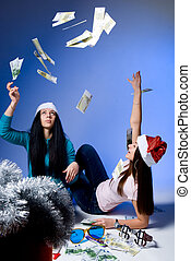 Girls in Santa hats, throw up banknotes.blue background