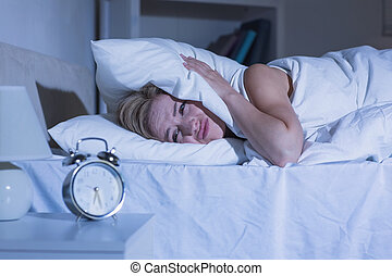 Woman covering ears with pillow as alarm clock rings - Young...
