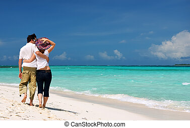 Young couple on the beach - Young loving couple walking...