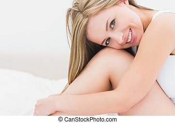 Portrait of smiling young woman in bed