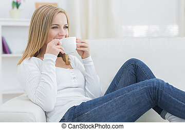Woman drinking coffee as she looks away on couch - Young...