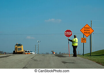Road Work - A worker controls traffic in a construction...