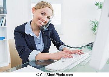 Portrait of business woman using phone and computer at desk...