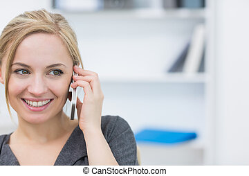 Close-up of business woman using mobile phone in office -...