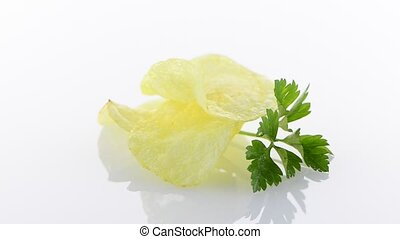 Potato chips and parsley isolated on white background.