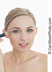 Close-up portrait of young woman putting on make-up over...