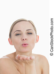 Close-up of cute young woman blowing a kiss over white...