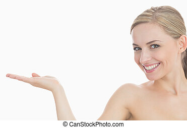 Portrait of beautiful young woman holding out open palm...