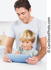 Father and son using tablet together in kitchen