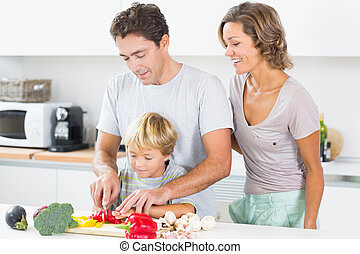 Mother watching father teaching son to chop vegetables