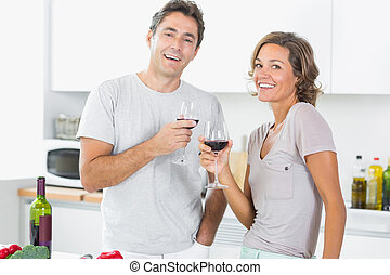 Smiling couple enjoying red wine together in the kitchen