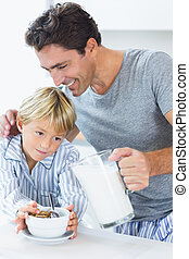 Smiling father pouring milk for sons cereal at breakfast