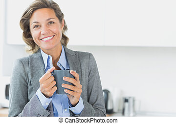 Smiling woman holding coffee mug in kitchen
