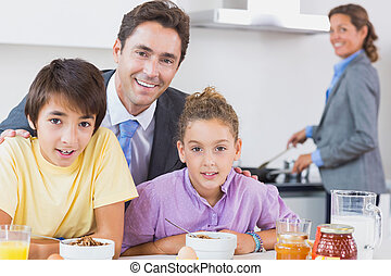 Father and children having breakfast while mother is cooking...