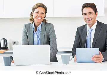 Happy couple with tablet and laptop in kitchen before work