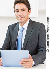 Man in suit using tablet