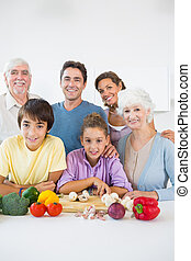 Multi generation family smiling in kitchen beside chopping...